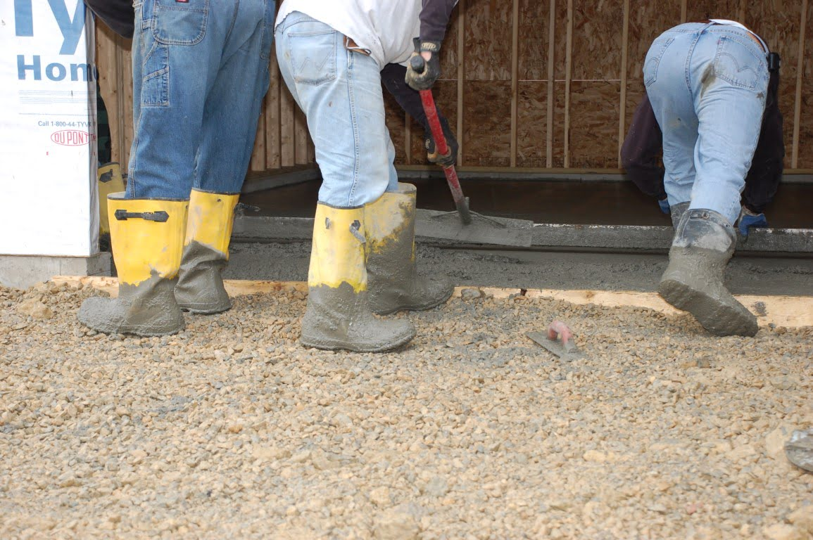 workers screeding fresh concrete floor in a garage