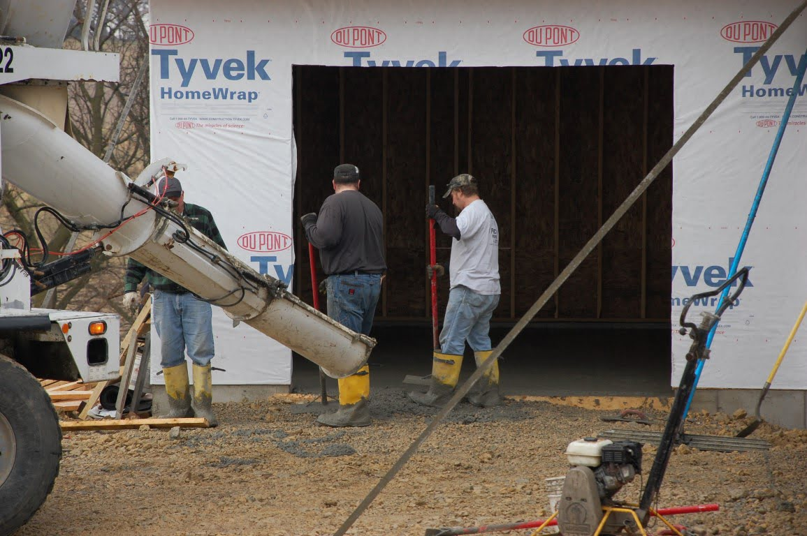 workers finishing up a concrete garage floor