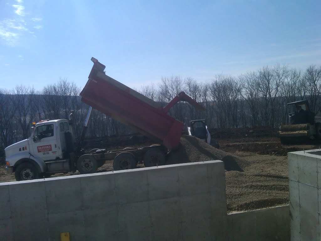 Photo of dump truck dropping aggregate stone
