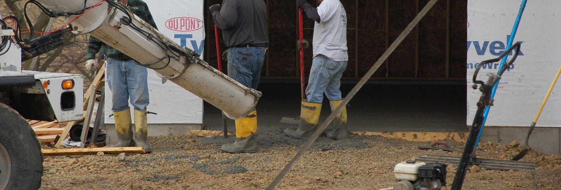 men pouring concrete driveway to unfinished garage