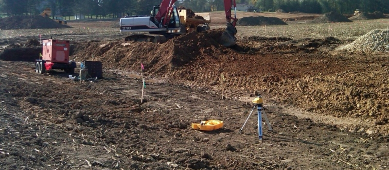 photo of backhoe excavating dirt into a pile