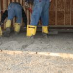 Workers leveling concrete for garage floor