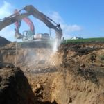 Photo of back hoe using hydraulic chisel to excavate the ground