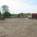 Backhoe excavating sod and dirt for new parking lot